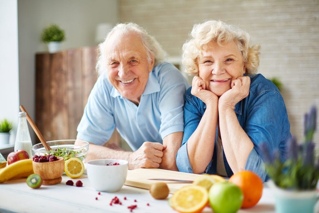 Seniors in kitchen with healthy fruits and vegetables